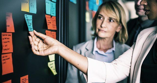 Team scrutinizing postits on glass wall