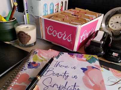 Image of box of index cards with other items on a desk
